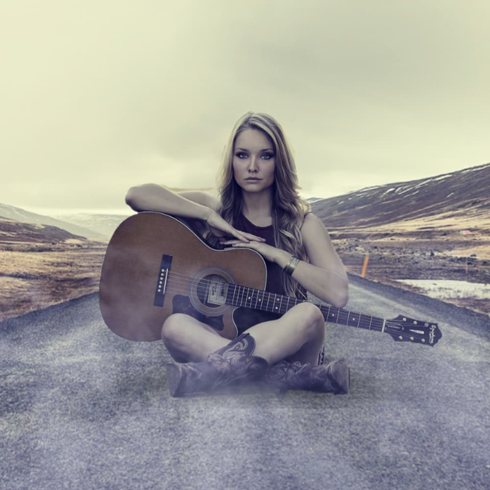 Blond girl with a guitar sitting on the road